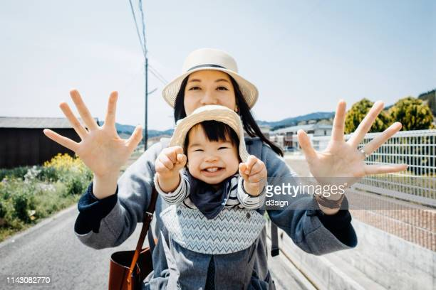 joyful mother and daughter smiling happily and cheering while on a trip walking along town in the countryside on a sunny day - 笑顔 ストックフォトと画像