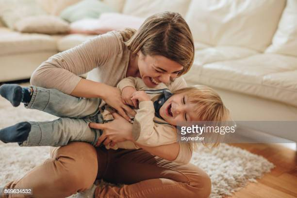 alegre mãe e seu filho pequeno se divertindo em casa. - fazendo cócegas - fotografias e filmes do acervo