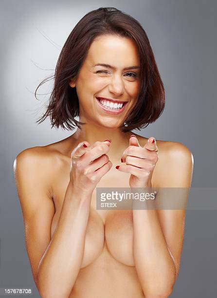 Joyful naked woman pointing at you against colored background
