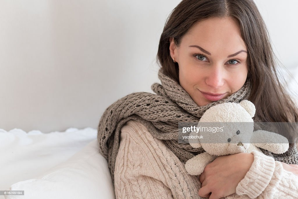 Joyful positive woman hugging a teddy bear : Foto de stock