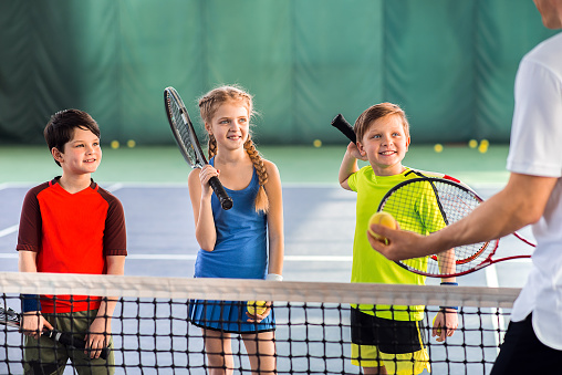 Joyful pupils learning to play tennis 690886826