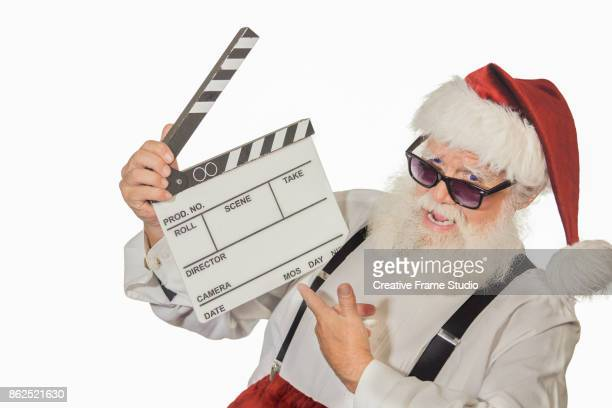 Joyful Santa Claus pointing a film clapperboard on white background