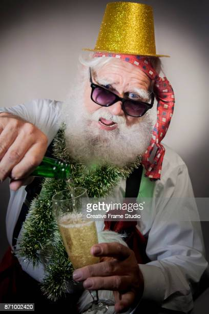 Joyful Santa Claus serving champagne on a glass wearing a gold  party hat.