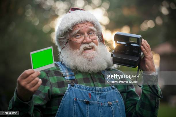 Joyful Santa Claus showing a photo taken with an instant camera