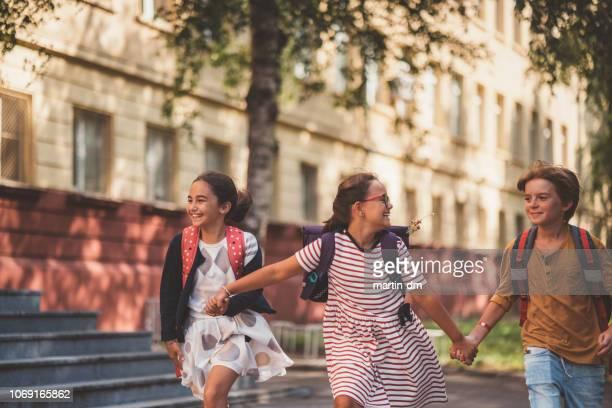 fröhliche schulkinder laufen außerhalb - schulkind stock-fotos und bilder