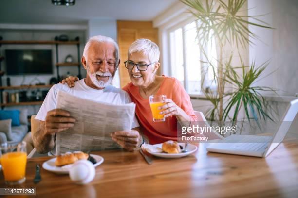 couples aînés joyeux lisant des journaux tout en mangeant le dessert - bonne posture photos et images de collection
