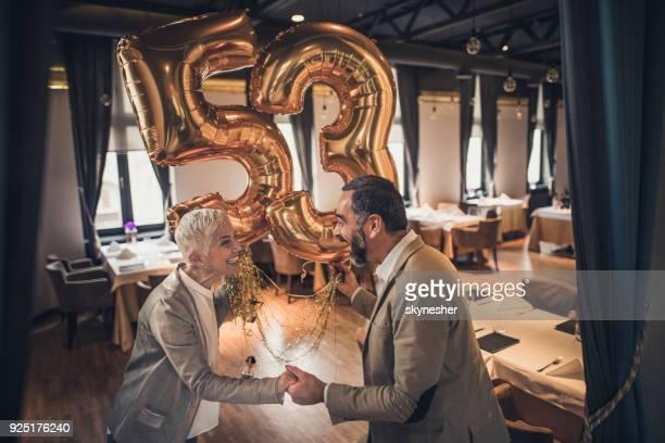 Vrolijke senior paar met helium ballonnen in een restaurant.