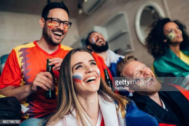 fröhlich fußball-enthusiasten, die unterstützung von verschiedenen teams beim spiel im fernsehen ansehen - weltmeisterschaft stock-fotos und bilder