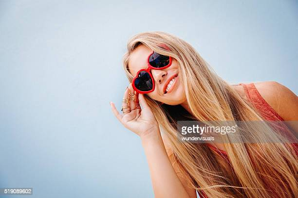 Joyful teen girl in casual clothes and sunglasses posing
