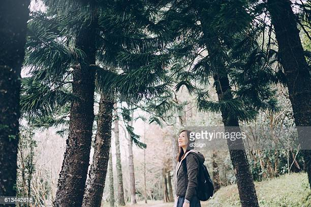 Joyful woman hikers with backpack looking up at trees while walking through forest
