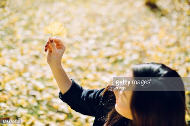 Joyful woman holding a yellow gingko leaf towards the sunlight in the forest