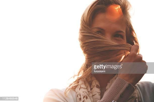 Joyful woman holding hair outdoors