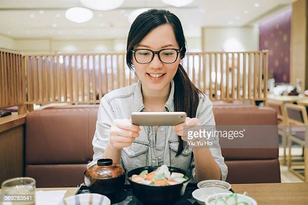 Joyful woman photographing her food at restaurant