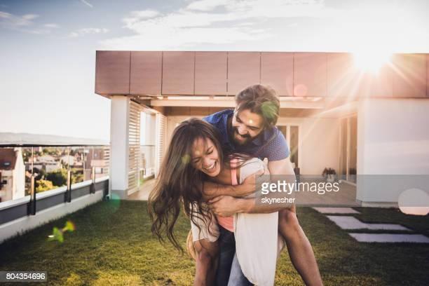 Fröhliche Frau Huckepack ihr Freund auf der Terrasse.
