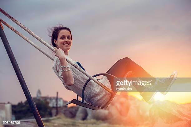 Joyful woman swinging at sunset