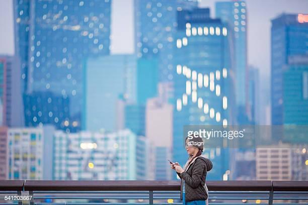Joyful woman text messaging on smartphone in city