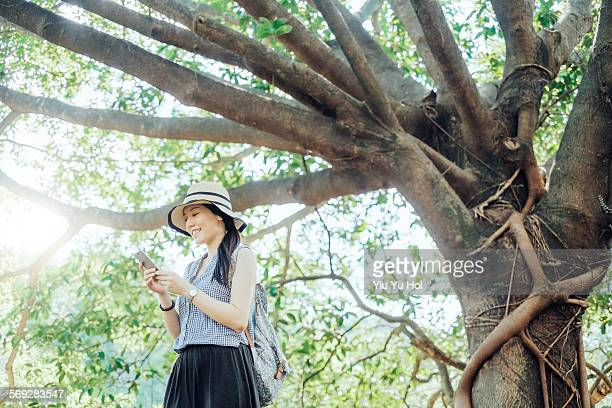 Joyful woman using smartphone in the woods