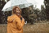 Joyful woman walking in rainy weather