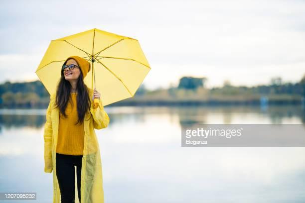 joyful woman walking in rainy weather - rainy season stock pictures, royalty-free photos & images