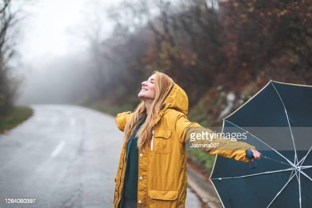 blije vrouw die in regenachtig weer loopt - mindfulness stockfoto's en -beelden