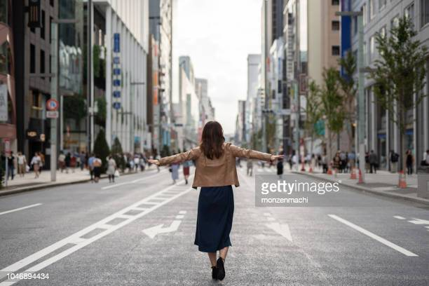 Joyful woman walking on the street with arms open