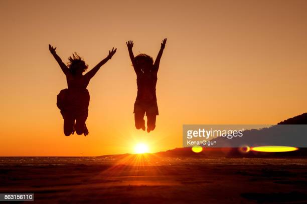 joyful women jumping up at the beach