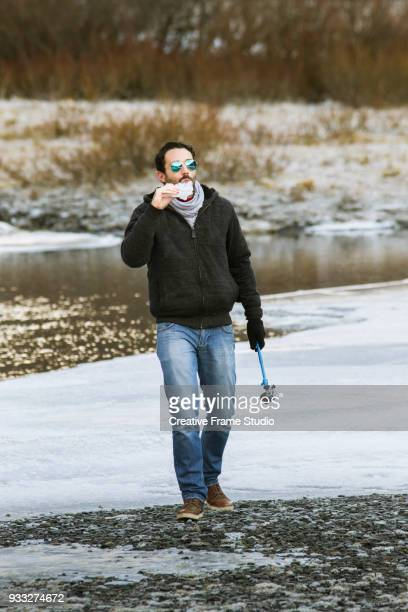 Joyful young adult man eating a piece of ice while walking on a winter scene