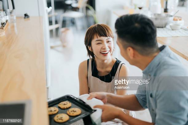 joyful young asian couple smiling at each other while taking out fresh home baked cookies from oven in a domestic kitchen - domestic life imagens e fotografias de stock