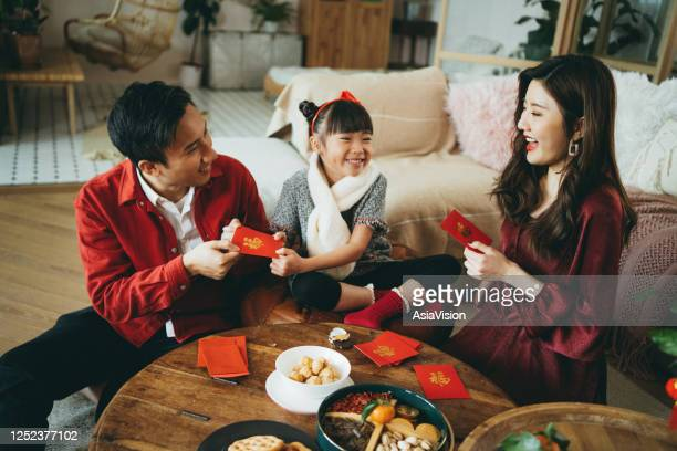 joyful young asian family celebrates chinese new year, parents giving red envelops (lai see) to their daughter and she receives them with both hands - prosperity stock pictures, royalty-free photos & images