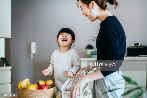 joyful young asian mother and happy little daughter coming home from grocery shopping, unpacking and arranging fresh and healthy organic fruits from a reusable mesh bag to rattan basket on the table. responsible shopping, zero waste, sustainable lifestyle - stay at home mother stock pictures, royalty-free photos & images