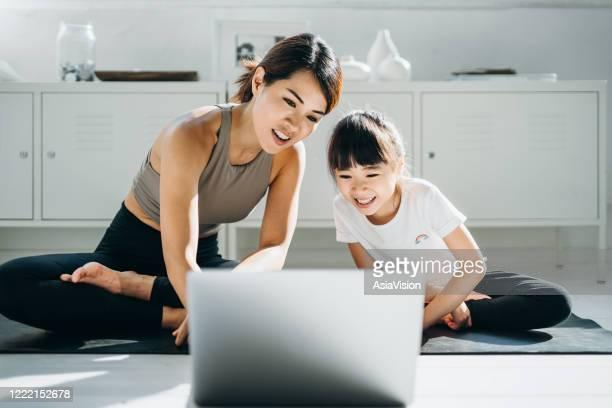 glad ung asiatisk mamma och lilla dotter gör online yoga klass tillsammans med en bärbar dator hemma - epidemiologi bildbanksfoton och bilder