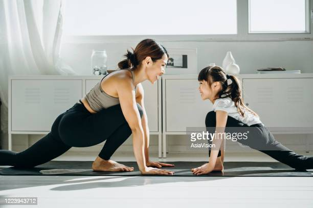 joyful young asian mother and little daughter exercising and practising yoga together at home - mental wellbeing stock pictures, royalty-free photos & images
