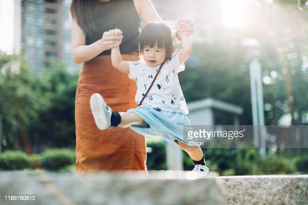joyful young asian mother holding hands of little daughter supporting and assisting her walking along on stone on a lovely sunny day - besonderes lebensereignis stock-fotos und bilder