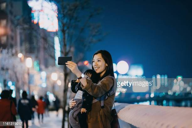 joyful young asian mother taking selfie with cute little daughter with smartphone by the promenade in the city at night - 福岡県 ストックフォトと画像