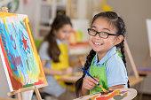 Joyful young female art student paints in a studio