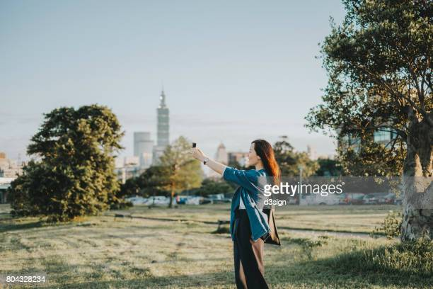 Joyful young lady taking pictures of beautiful scenics in park with smartphone during sunset