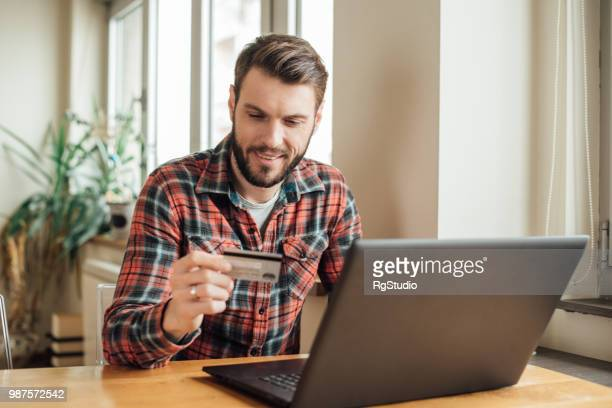 Joyful young man buys on the Internet with credit card