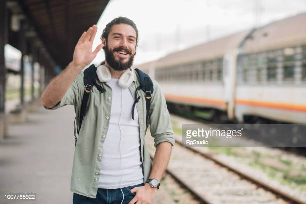Joyful young man waving hand at train station