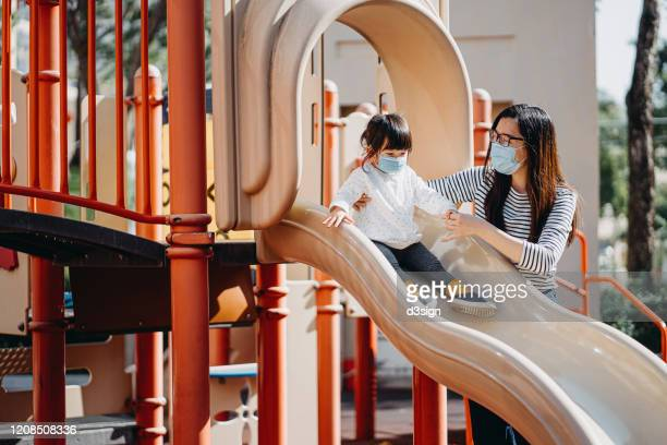 joyful young mother with little daughter wearing surgical mask to prevent the spread of cold and flu and viruses. they are having fun and playing slide in outdoor playground - slide play equipment stock pictures, royalty-free photos & images