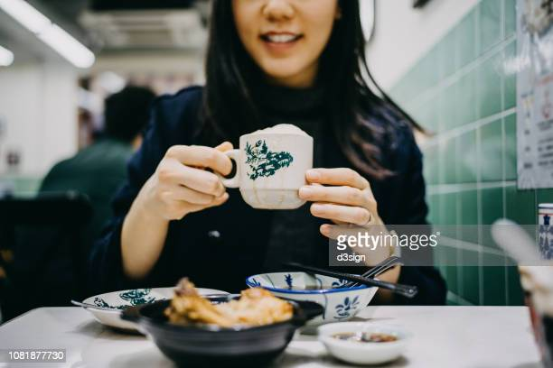 joyful young woman enjoying bakuteh and teh tarik in a traditional restaurant - malaysian culture stock pictures, royalty-free photos & images