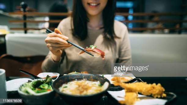 joyful young woman enjoying sushi, seafood tempura, soup udon, salad and green tea in a japanese restaurant - aziatische etniciteit stockfoto's en -beelden