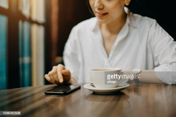 joyful young woman having a relaxing time in cafe enjoying coffee and text messaging on smartphone - asian drink stock photos and pictures