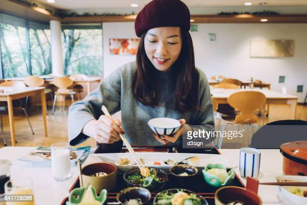 Joyful young woman is having meal in a Japanese restaurant