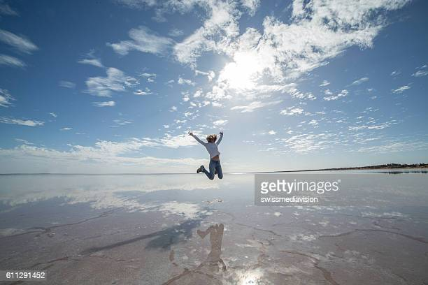 Joyful young woman jumping mid-air on salt lake