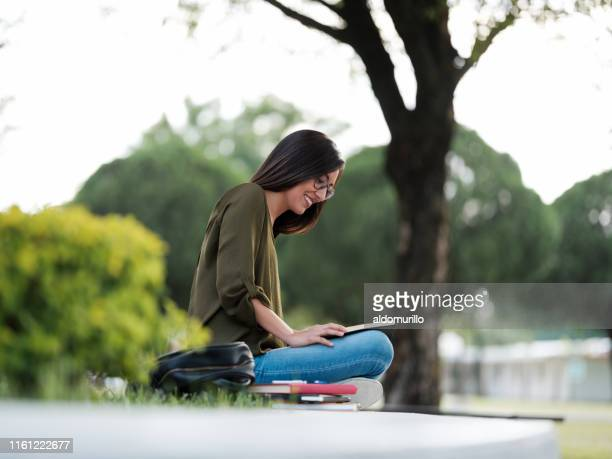 joyful young woman reading a book - prayer book stock pictures, royalty-free photos & images