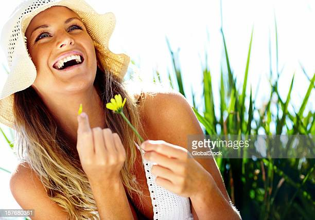 Joyful young woman with flower enjoying outdoors and smiling
