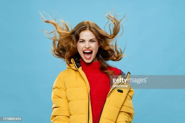 joyful young woman with red hair in warm winter clothes laughing fun - red trousers stock pictures, royalty-free photos & images