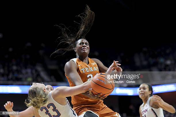 Joyner Holmes of the Texas Longhorns commits a charging foul as she crashes into Katie Lou Samuelson of the Connecticut Huskies as she drives to the...