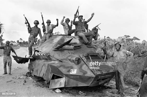 Joyous Biafran soldiers seen here cheering with guns in the air as they sit atop a destroyed Nigerian army armoured personnel carrier during the...