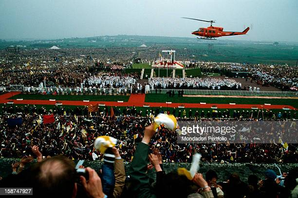 A joyous crowd of Christian believers greets the arrival of papal helicopter in the occasion of an official visit of the Holy Father onboard is Pope...